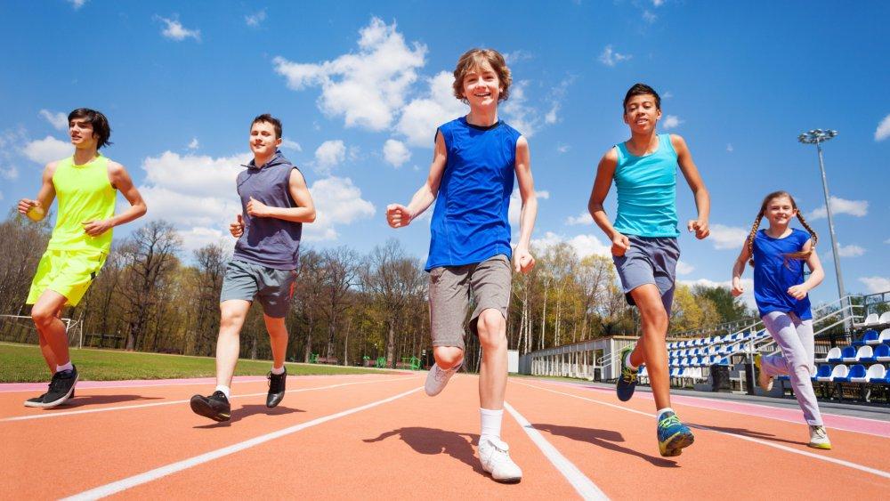 five-happy-teenage-kids-running-on-the-stadium-picture-id583849568